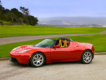 AUT 09 RK0886 01 © Kimball Stock Tesla Roadster Electric Car Red 3/4 Side View On Pavement By Grass And Trees