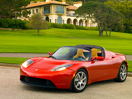 AUT 09 RK0887 01 © Kimball Stock Tesla Roadster Electric Car Red 3/4 Front View On Pavement By Grass And Trees