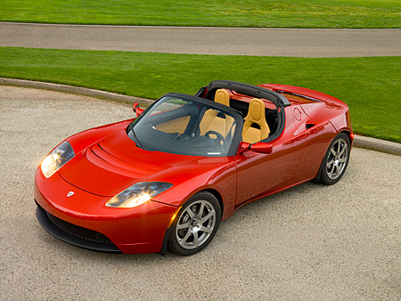 AUT 09 RK0888 01 © Kimball Stock Tesla Roadster Electric Car Red Overhead 3/4 Front View On Pavement By Grass And Trees