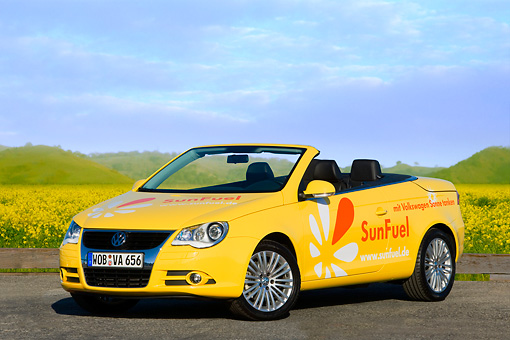 AUT 09 RK1032 01 © Kimball Stock Volkswagen Eos SunFuel Prototype Yellow 3/4 Front View On Pavement By Hills Sky