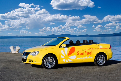 AUT 09 RK1035 01 © Kimball Stock Volkswagen Eos SunFuel Prototype Yellow 3/4 Front View On Pavement By Water Sky