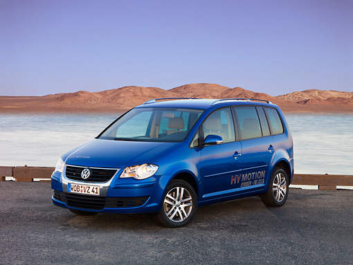 AUT 09 RK1042 01 © Kimball Stock Volkswagen Touran HyMotion Prototype Blue 3/4 Front View On Pavement By Water Hills Sky