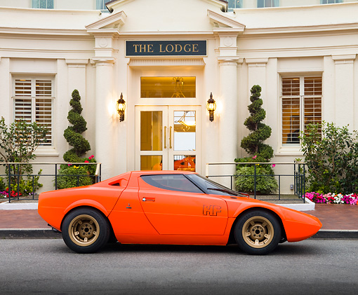 AUT 09 RK1064 01 © Kimball Stock 1970 Lancia Stratos HF Prototype Bertone Coupe DayGlo Red Profile View On Pavement By Mansion