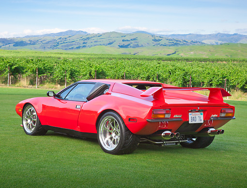 AUT 10 RK0038 01 © Kimball Stock 1974 De Tomaso Pantera Red 3/4 Rear View On Grass By Vineyard