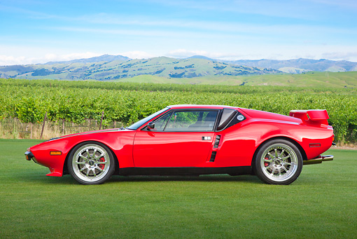 AUT 10 RK0039 01 © Kimball Stock 1974 De Tomaso Pantera Red Profile View On Grass By Vineyard