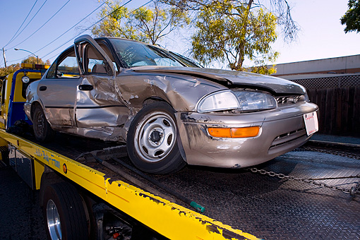AUT 11 RK0004 01 © Kimball Stock Tow Truck Towing Wrecked Geo Prizm On Flatbed