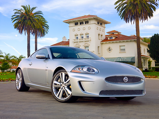 AUT 12 BK0001 01 © Kimball Stock 2011 Jaguar XKR Coupe Silver 3/4 Front View On Pavement By Palm Trees And Building