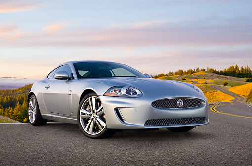 AUT 12 BK0002 01 © Kimball Stock 2011 Jaguar XKR Coupe Silver 3/4 Front View On Road By Hillside