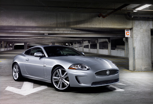 AUT 12 BK0003 01 © Kimball Stock 2011 Jaguar XKR Coupe Silver 3/4 Front View In Parking Garage At Night