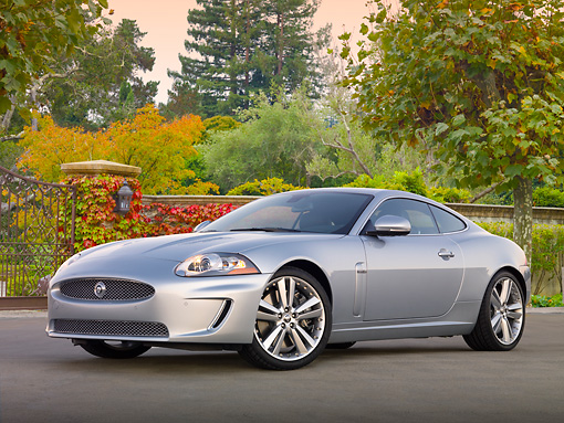 AUT 12 BK0004 01 © Kimball Stock 2011 Jaguar XKR Coupe Silver 3/4 Front View On Pavement By Gate And Autumn Trees