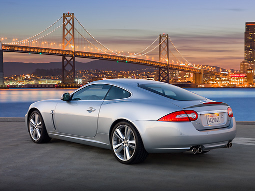 AUT 12 BK0005 01 © Kimball Stock 2011 Jaguar XKR Coupe Silver 3/4 Rear View On Pavement By San Francisco Bay Bridge At Dusk