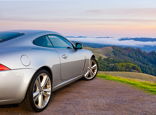 AUT 12 BK0006 01 © Kimball Stock 2011 Jaguar XKR Coupe Silver 3/4 Rear View On Gravel Overlooking Hills