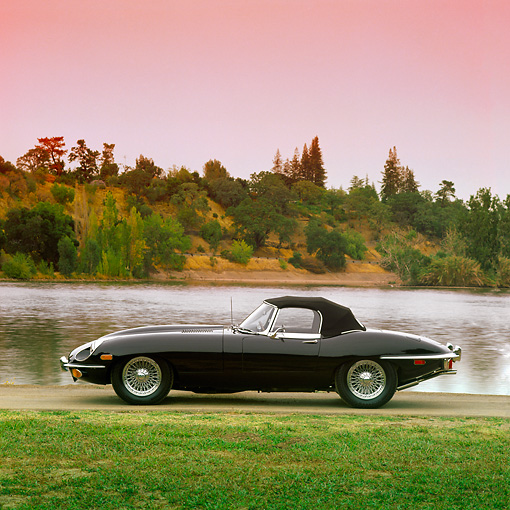 AUT 12 RK0024 03 © Kimball Stock 1969 Black Jaguar XKE Conv Side View By Lake And Grass At Dusk