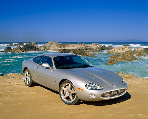 AUT 12 RK0126 07 © Kimball Stock 2001 Jaguar XKR Silverstone Coupe 3/4 Front View On Sand By Ocean And Rocks Blue Sky