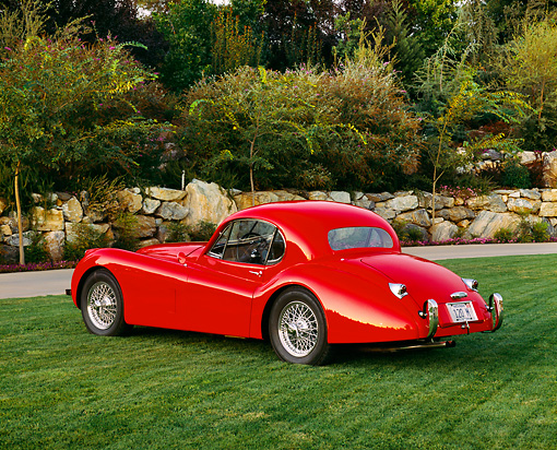 AUT 12 RK0154 05 © Kimball Stock 1954 Jaguar XK120 FHC Red Rear 3/4 View On Grass By Trees