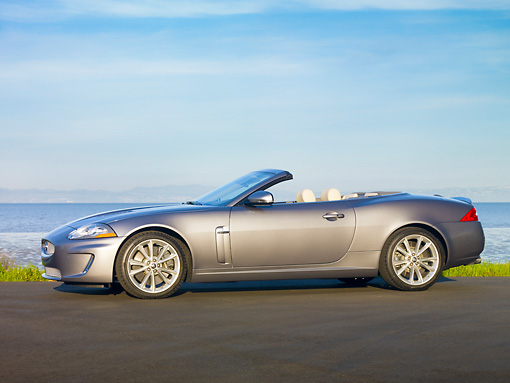AUT 12 RK0341 01 © Kimball Stock 2010 Jaguar XKR Convertible Silver Profile On Pavement By Water