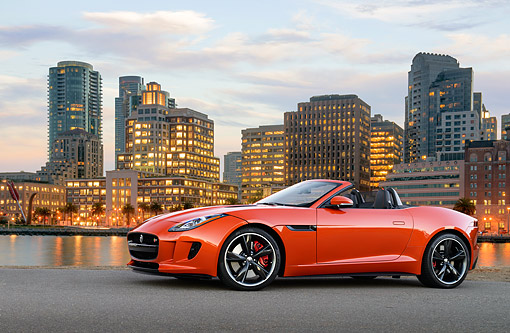 AUT 12 RK0380 01 © Kimball Stock 2014 Jaguar F-Type Orange 3/4 Side View On Pavement By Water And Skyscrapers At Dusk