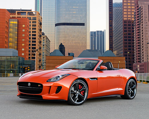 AUT 12 RK0381 01 © Kimball Stock 2014 Jaguar F-Type Orange 3/4 Front View On Pavement By Skyscrapers