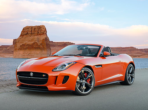 AUT 12 RK0383 01 © Kimball Stock 2014 Jaguar F-Type Orange 3/4 Front View On Pavement By Water And Red Rock