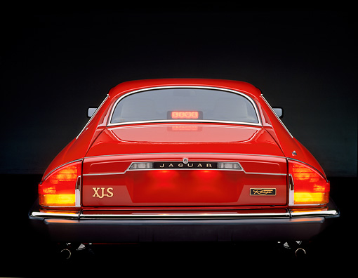 AUT 12 RK0001 08 © Kimball Stock 1990 Red Jaguar XJS Rouge Rear View Brake Lights On Studio Background