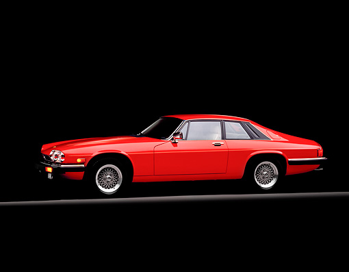 AUT 12 RK0003 02 © Kimball Stock 1990 Red Jaguar XJS Rouge Side View On Red Line Parking Lights On Studio Background