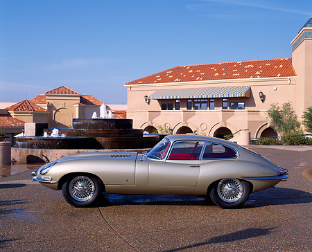 AUT 12 RK0013 08 © Kimball Stock 1961 Jaguar XKE Coupe E-Type Gold Profile On Pavement By Building And Water Fountain Blue Sky