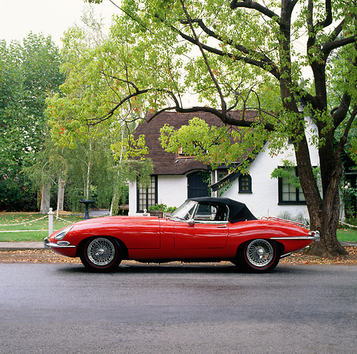 AUT 12 RK0018 02 © Kimball Stock 1964 Red Jaguar XKE Conv Side View In Front House By Trees