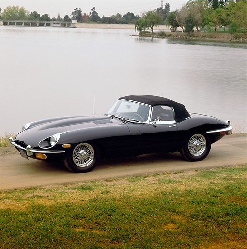 AUT 12 RK0023 01 © Kimball Stock 1969 Black Jaguar XKE 3/4 Side View By Lake And Trees At Dusk