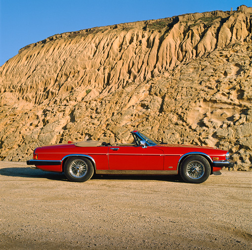 AUT 12 RK0032 01 © Kimball Stock 1988 Red Jaguar XJ5 Side View Rock Mountain Background Blue Sky