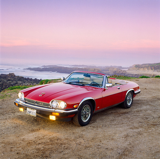 AUT 12 RK0038 09 © Kimball Stock 1988 Red Jaguar XJ5 Conv 3/4 Front View On Dirt Road Headlights On At Dusk
