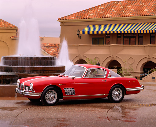 AUT 12 RK0054 05 © Kimball Stock 1958 Red Jaguar Ghia Coupe XK140 3/4 Side View On Wet Pavement By Water Fountain