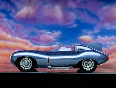 AUT 12 RK0056 01 © Kimball Stock 1955 Jaguar XKD 528 D Type Roadster Light Blue Profile On Mylar Floor Pink Clouds Background Studio