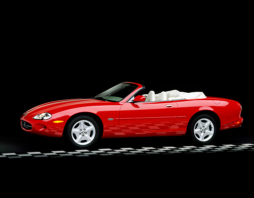 AUT 12 RK0061 02 © Kimball Stock 1999 Jaguar XK8 Convertible Phoenix Red 3/4 Side View On Checkerboard Line Parking Lights On Studio
