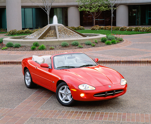 AUT 12 RK0066 01 © Kimball Stock 1999 Jaguar XK8 Convertible Phoenix Red Overhead 3/4 Front On Pavement Headlights On By Fountain