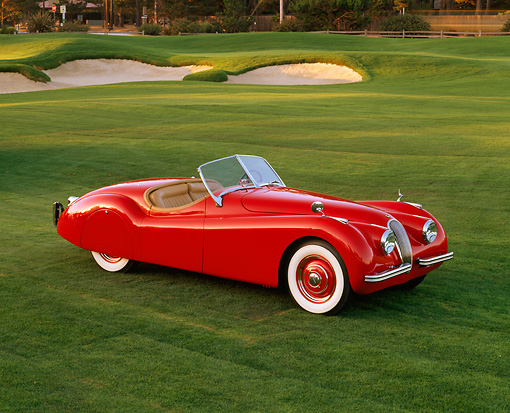 AUT 12 RK0086 05 © Kimball Stock 1951 Jaguar XK120 Roadster Red 3/4 Front View On Grass