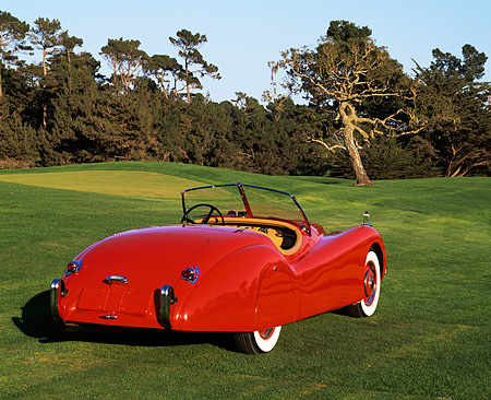AUT 12 RK0087 02 © Kimball Stock 1951 Jaguar XK120 Roadster Red 3/4 Rear View On Grass Trees Background