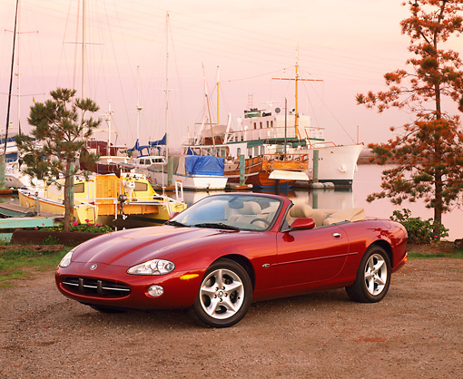AUT 12 RK0089 01 © Kimball Stock 2001 Jaguar XK8 CNV Convertible Red 3/4 Front View On Dirt By Harbor
