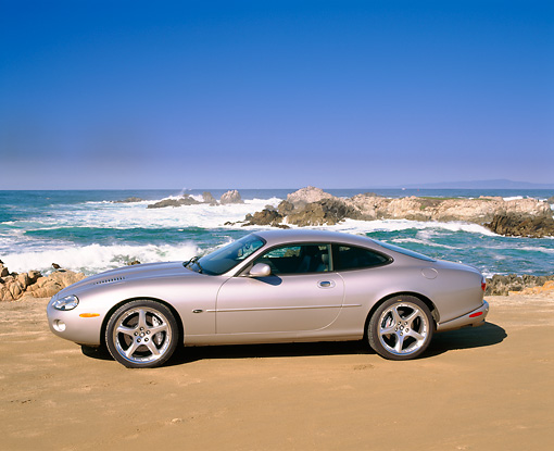 AUT 12 RK0121 02 © Kimball Stock 2001 Jaguar XKR Silverstone Coupe Side View On Sand By Ocean And Rocks Blue Sky