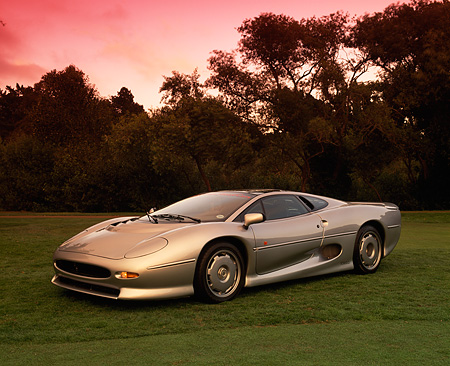 AUT 12 RK0141 05 © Kimball Stock 1994 Jaguar XJ220 Silver Side 3/4 View On Grass Trees Background