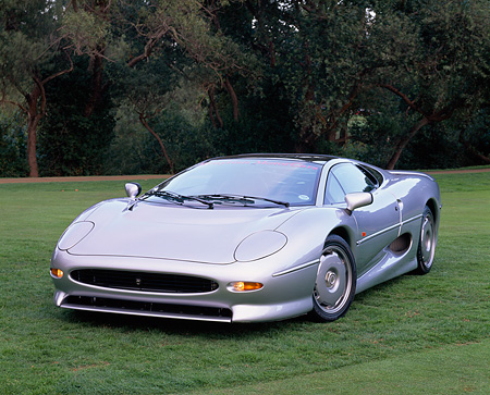 AUT 12 RK0142 01 © Kimball Stock 1994 Jaguar XJ220 Silver Front 3/4 View On Grass Trees Background