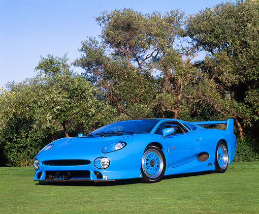 AUT 12 RK0147 03 © Kimball Stock 1994 Jaguar XJ220 Blue 3/4 Low Front View On Grass Trees Blue Sky