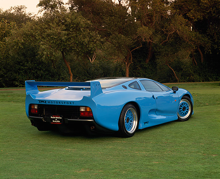 AUT 12 RK0150 01 © Kimball Stock 1994 Jaguar XJ220 Blue 3/4 Rear View On Grass Trees Background