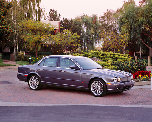 AUT 12 RK0173 03 © Kimball Stock 2004 Jaguar XJR Gray 3/4 Side View On Pavement By Flowers And Trees