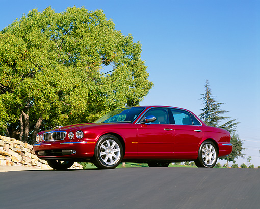 AUT 12 RK0176 03 © Kimball Stock 2004 Jaguar XJ Burgundy 3/4 Front View Low Angle On Pavement Hill Trees Blue Sky