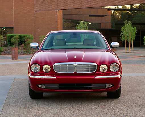 AUT 12 RK0184 02 © Kimball Stock 2004 Jaguar XJ Burgundy Head On View By Building