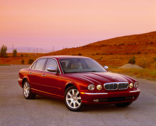 AUT 12 RK0187 01 © Kimball Stock 2004 Jaguar XJ Burgundy 3/4 Front View On Pavement By Grass Hill Filtered