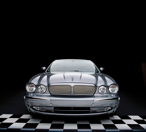 AUT 12 RK0191 13 © Kimball Stock 2004 Jaguar XJR Gray Wide Angle Head On View Checkered Floor Studio