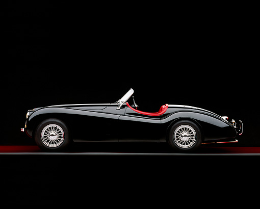AUT 12 RK0197 01 © Kimball Stock 1954 Jaguar XK120 M Roadster Black Profile On Red Floor Gray Line Studio