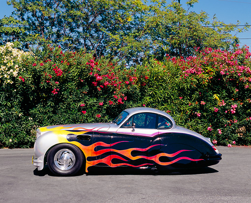 AUT 12 RK0204 01 © Kimball Stock 1952 Jaguar MK VII Silver With Flames Side View On Pavement By Pink Flower Bush