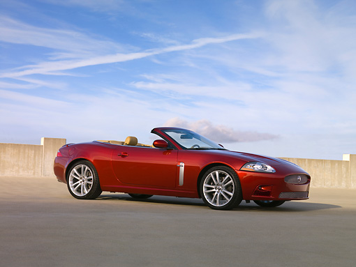 AUT 12 RK0256 01 © Kimball Stock 2007 Jaguar XK Convertible Red Low 3/4 Side View On Pavement